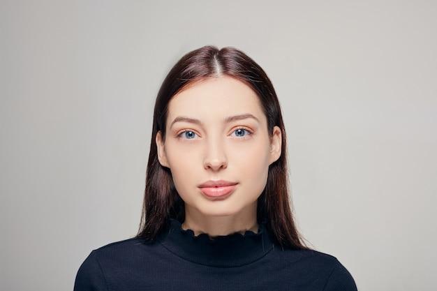 Schöne frau mit natürlichem make-up. frauen mit sauberer frischer haut, dunklem gehör und blauen augen.