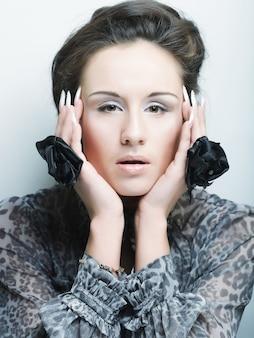 Schöne frau mit natürlichem make-up mit hand, die großen blumenring trägt.