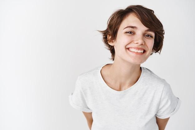 Schöne frau mit natürlicher glatter haut ohne make-up, die glücklich und lächelnd posiert und im t-shirt gegen weiße wand steht