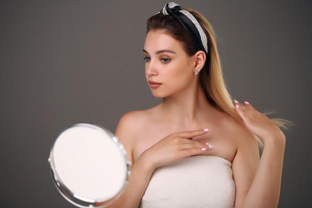 Schöne frau mit natürlicher mode des langen haares bilden kosmetisches spa-schönheitskonzept der frau, die am tisch nahe dem spiegel sitzt.