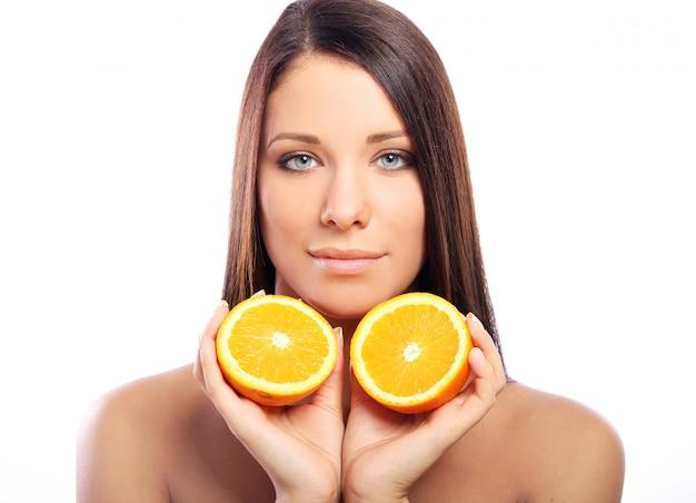 Schöne frau mit orange in den händen