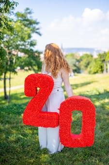 Schöne frau mit papiernummer mit blumen in handdekorationen mit eigenen händen gemacht kleines b...