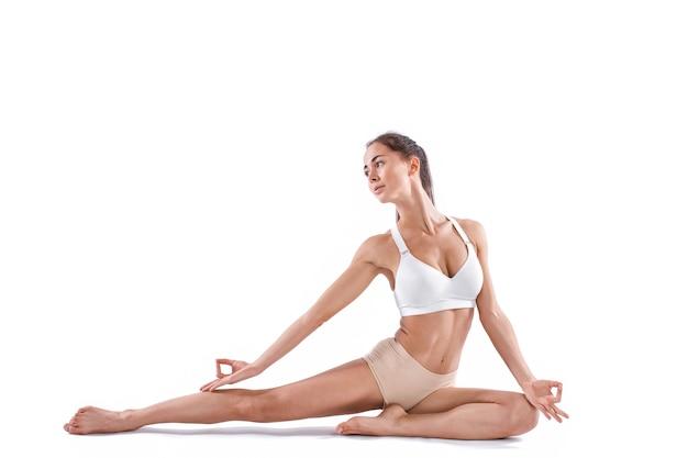 Schöne frau mit perfektem körper, der yoga praktiziert, wirft in voller länge im studio auf weißem hintergrund auf. konzept des gesunden lebens.