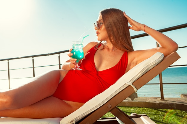 Schöne frau mit perfektem körper sonnenbaden auf sonnenliege