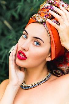 Schöne frau mit perfektem make-up und orangefarbenem kopftuch, roten großen lippen, blauen augen, händen auf dem kopf
