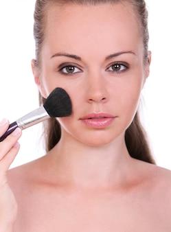 Schöne frau mit pinsel zum schminken