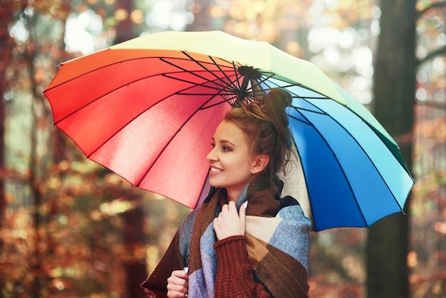 Schöne frau mit regenbogenregenschirm im herbstlichen wald