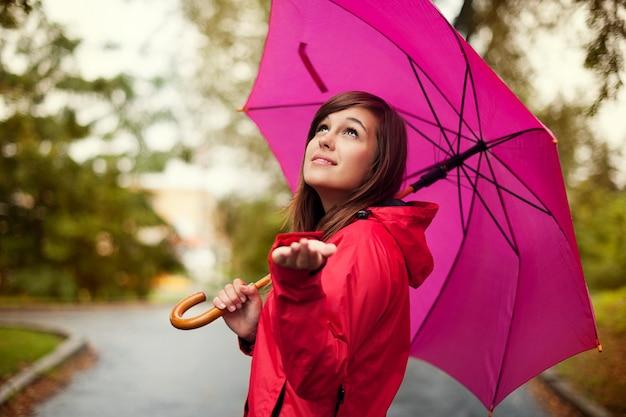 Schöne frau mit regenschirm, der für regen prüft