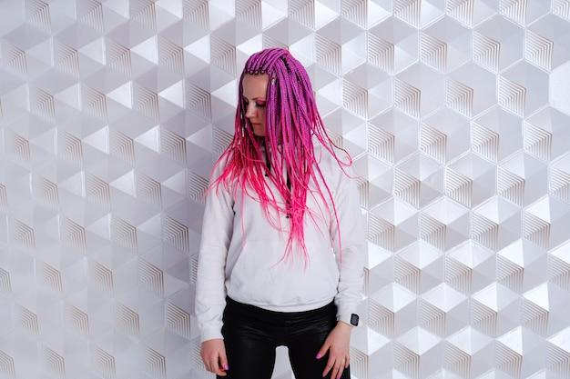 Schöne frau mit rosa haaren im weißen hoodie über futuristischem hintergrund. augmented-reality-spiel, zukunftstechnologie, ki-konzept. vr.