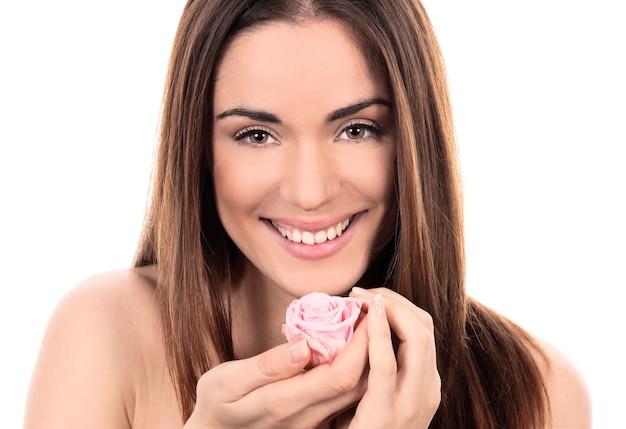 Schöne frau mit rosa rose auf weißem hintergrund