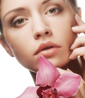 Schöne frau mit rosafarbener blume