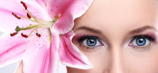 Schöne frau mit rosafarbener lilienblume