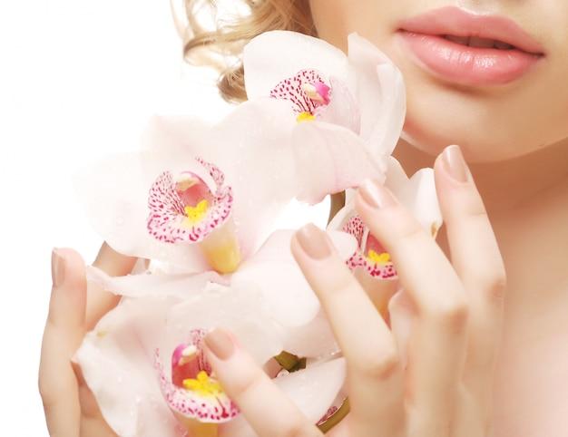 Schöne frau mit rosafarbener orchidee