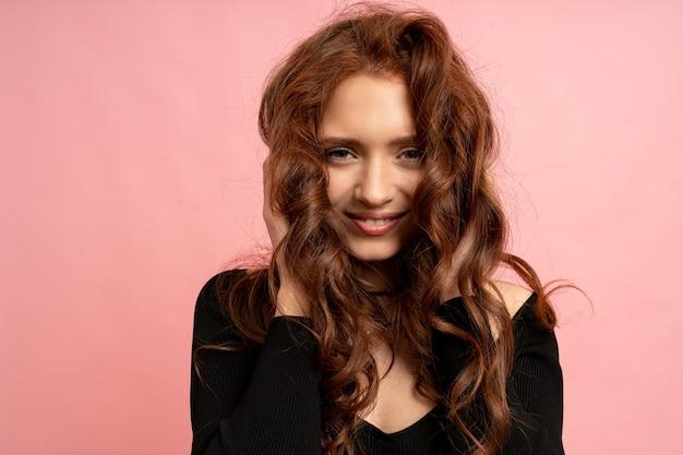 Schöne frau mit rotem kopf, die über rosa wand aufwirft. gewellte haare. schönes lächeln.