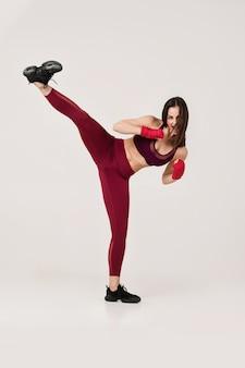 Schöne frau mit rotem verpackenband auf dem handgelenk, das aufwärmen tut, trainiert