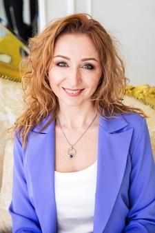 Schöne frau mit roten haaren in einem lila anzug sitzt auf einem goldenen sofa.