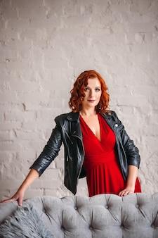 Schöne frau mit roten haaren und im roten kleid mit lederjacke steht hinter einer grauen couch