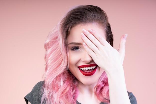 Schöne frau mit roten lippen, die ihr linkes auge mit einer hand bedecken