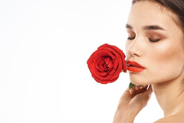 Schöne frau mit roter rose nahe gesicht make-up nackte schultern porträt.
