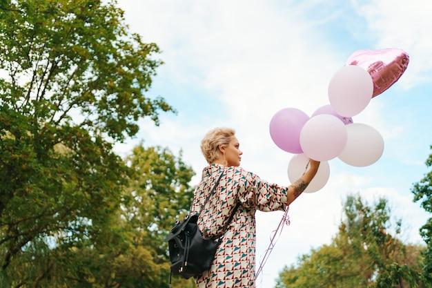 Schöne frau mit rucksack, der glücklich mit rosa luftballons im park geht. konzept für freiheit und gesunde frauen.