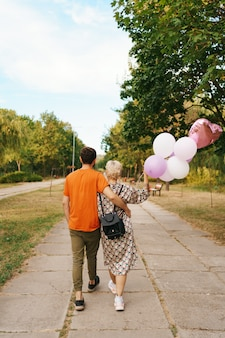 Schöne frau mit rucksack und lässigem mann, der glücklich mit rosa luftballons im park geht. konzept für freiheit und gesunde frauen.