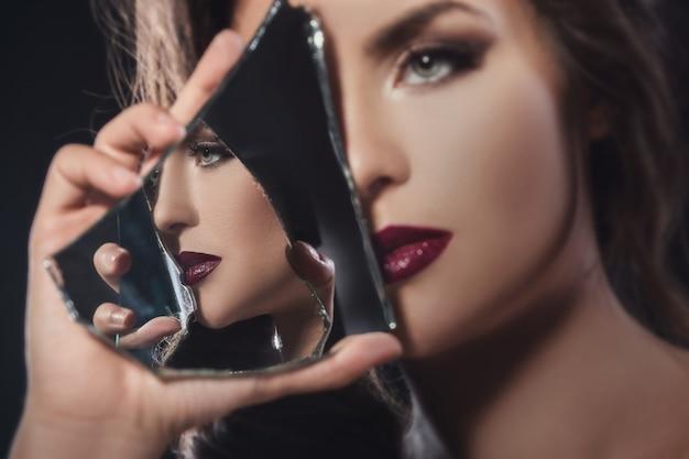 Schöne frau mit scherben des spiegels