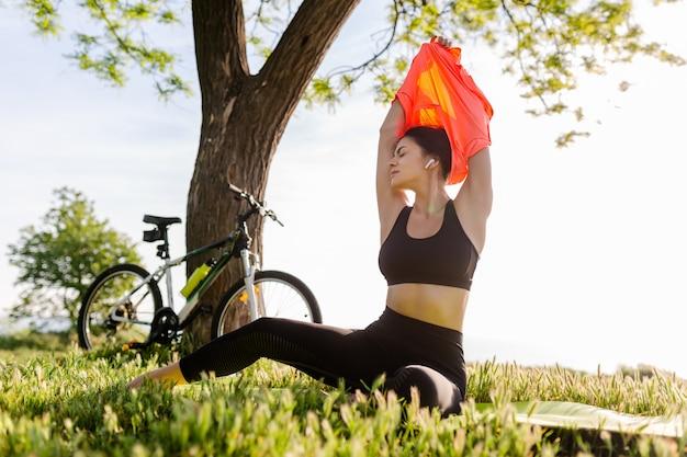 Schöne frau mit schmaler passform, die morgens im park auf yogamatte sport treibt
