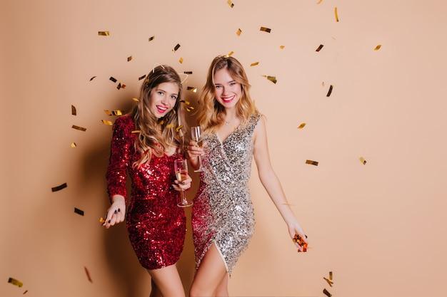 Schöne frau mit schwarzer maniküre, die mit schüchternem lächeln aufwirft, champagner am fest trinkend