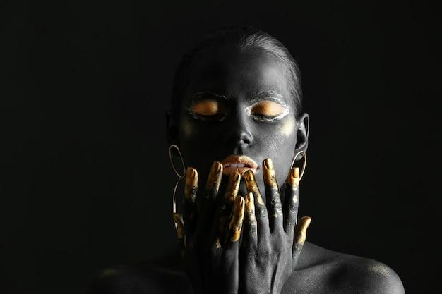 Schöne frau mit schwarzer und goldener farbe auf ihrem körper gegen dunkelheit