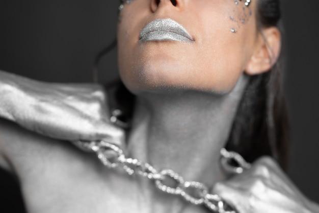 Schöne frau mit silberner farbe auf ihrer haut und ihren haaren bricht die kette um ihren hals.