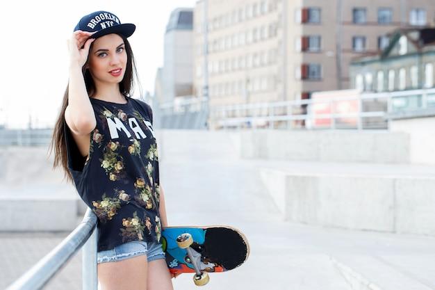 Schöne frau mit skateboard