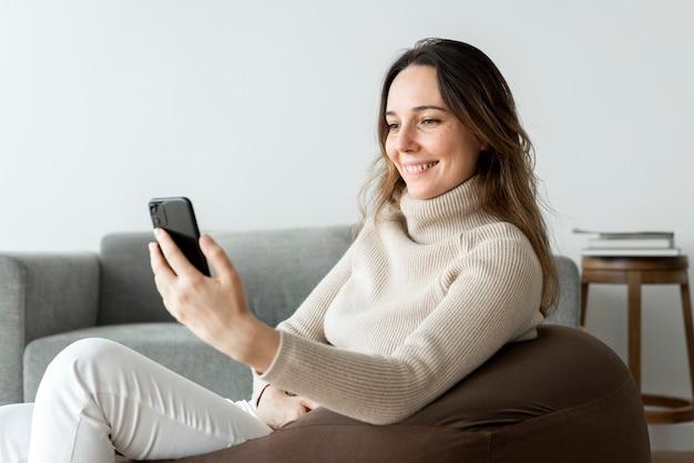 Schöne frau mit smartphone auf einem sitzsack