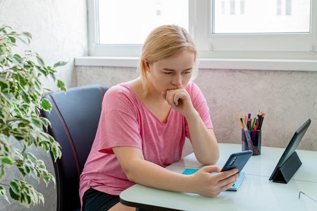 Schöne frau mit smartphone und tablet. von zu hause aus arbeiten. online einkaufen