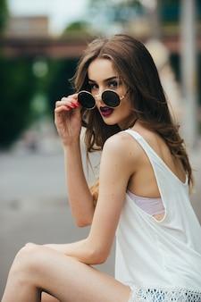Schöne frau mit sonnenbrille, die auf dem asphalt sitzt