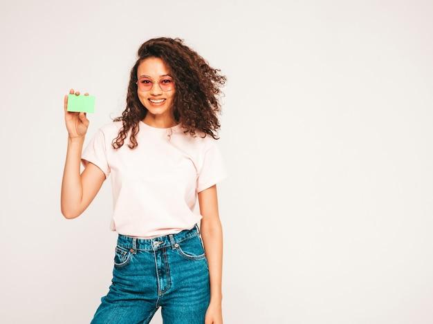 Schöne frau mit sonnenbrille, die grüne kreditkarte zeigt
