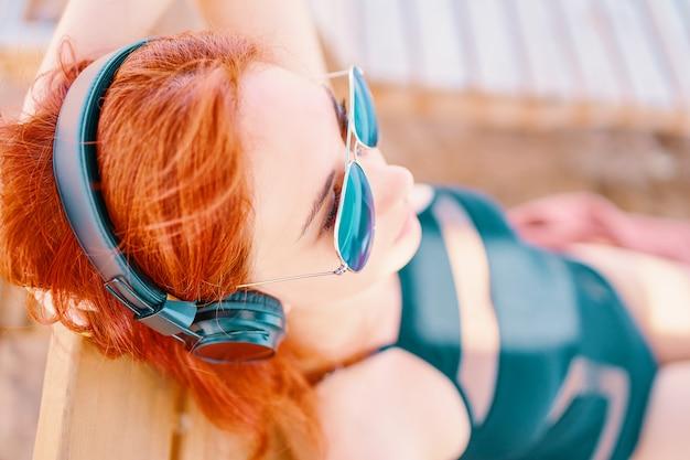 Schöne frau mit sonnenbrille musik am strand hören.