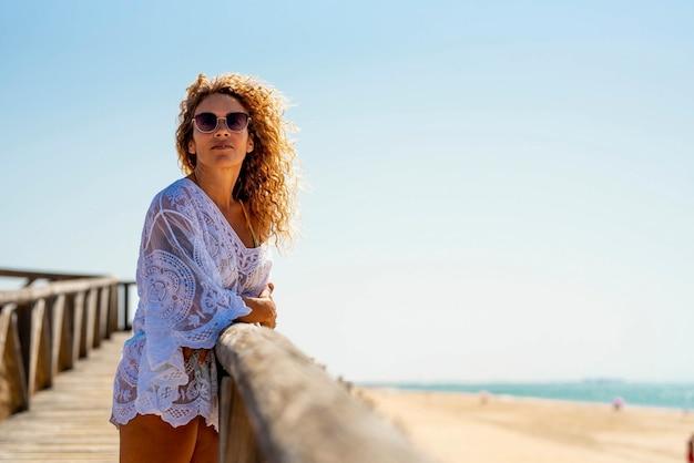 Schöne frau mit sonnenbrille und weißem sommerkleid, die auf einem holzsteg oder einem steg am sandstrand mit meerblick gegen den klaren blauen himmel steht. frau, die am strand urlaub macht