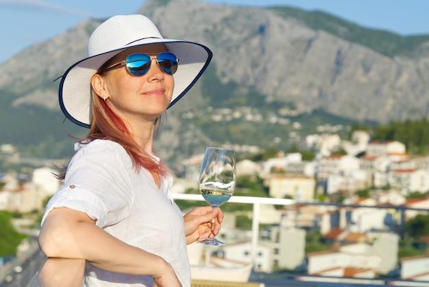 Schöne frau mit strohhut, die den abend mit weinglas auf der terrasse des resort-luxushotels genießt