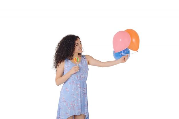 Schöne frau mit süßem lutscher und baloons.