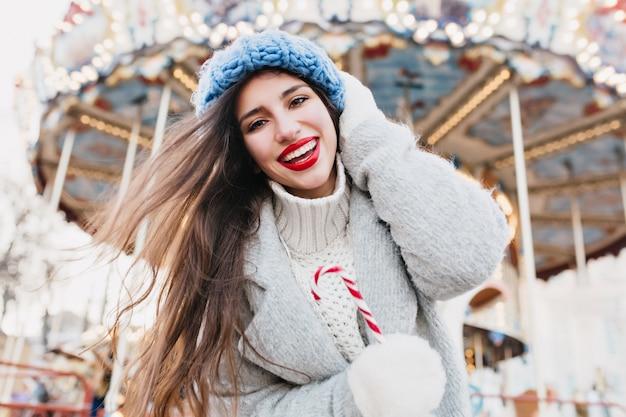 Schöne frau mit süßer zuckerstange, die nahe karussell in weihnachten aufwirft. foto im freien des glücklichen dunkelhaarigen mädchens mit lutscher, das im vergnügungspark im winter entspannt.