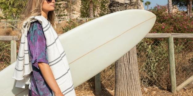 Schöne frau mit surfbrett am strand