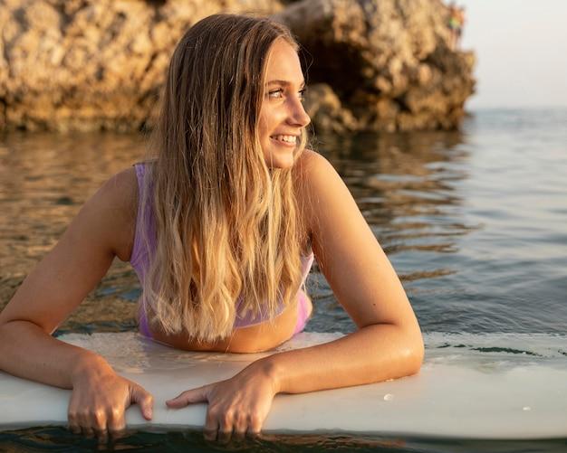Schöne frau mit surfbrett im wasser