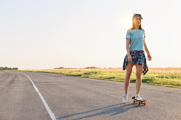 Schöne frau mit t-shirt, kurz- und haarband, skateboarding auf der straße, blick in die ferne, zeit allein mit vergnügen, aktivem und gesundem lebensstil.