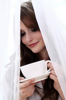 Schöne frau mit tasse heißem kaffee