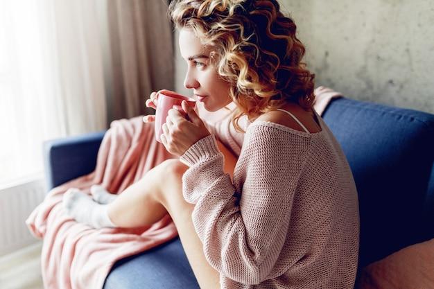 Schöne frau mit tasse kaffee auf dem sofa