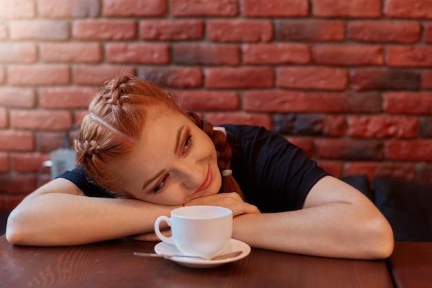 Schöne frau mit tasse kaffee liegt auf tisch und schaut lächelnd beiseite