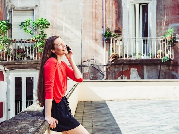 Schöne frau mit telefon auf dem hintergrund der alten häuser