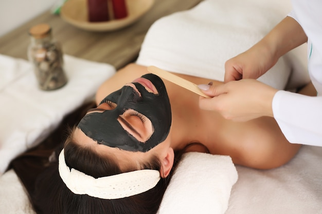 Schöne frau mit ton gesichtsmaske von kosmetikerin anwenden.