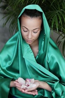 Schöne frau mit traditioneller indischer tracht und blume auf den händen