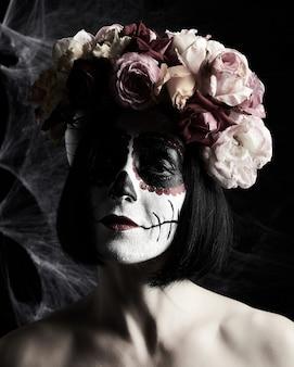 Schöne frau mit traditioneller mexikanischer totenmaske. calavera catrina. zuckerschädel make-up. frau, gekleidet in einen rosenkranz